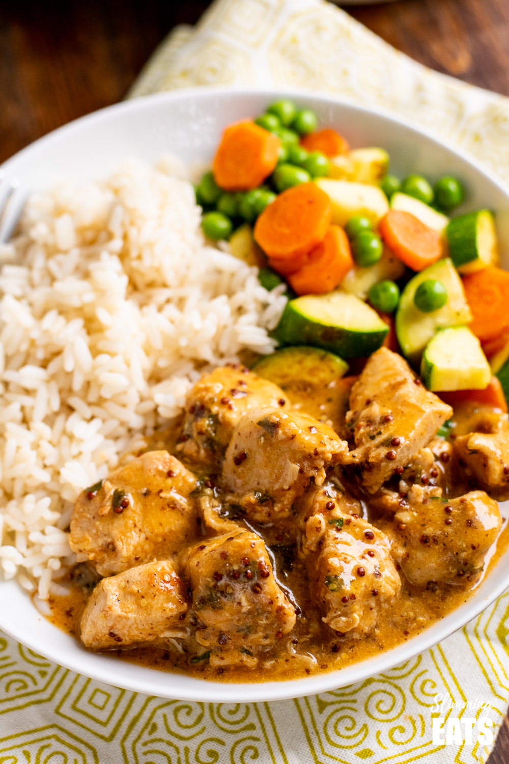 close up of instant pot honey mustard chicken in white bowl with rice and vegetables