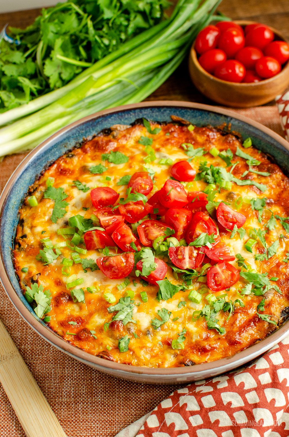 Mexican spaghetti squash bake in oven proof dish with green onions and tomatoes in background
