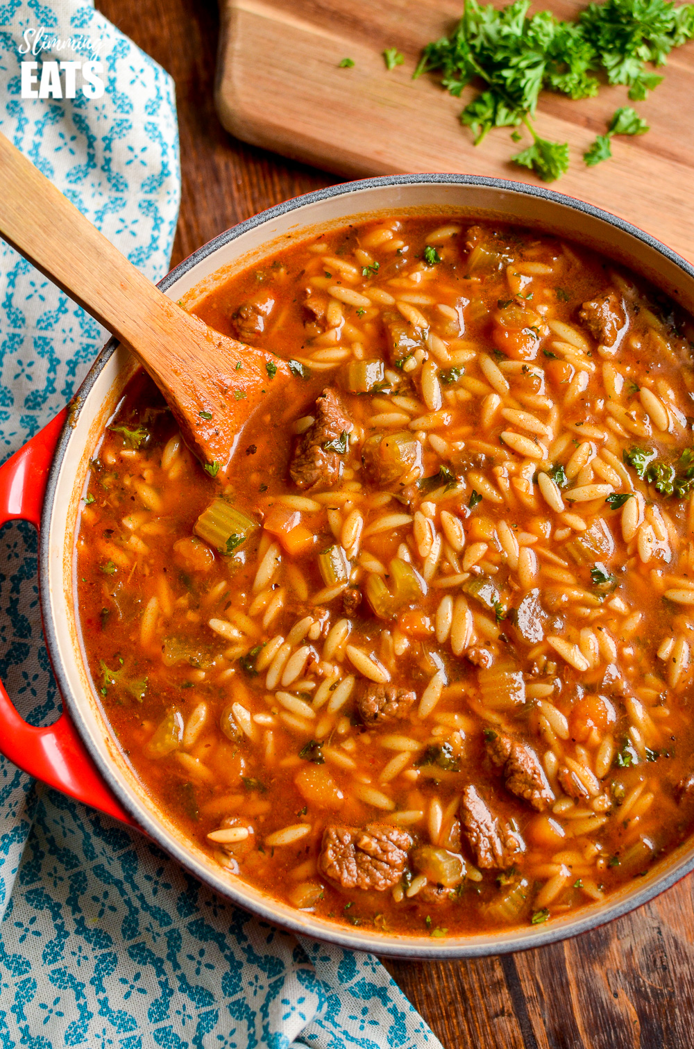 beef celery orzo stew in red dutch oven pot with wooden spoon