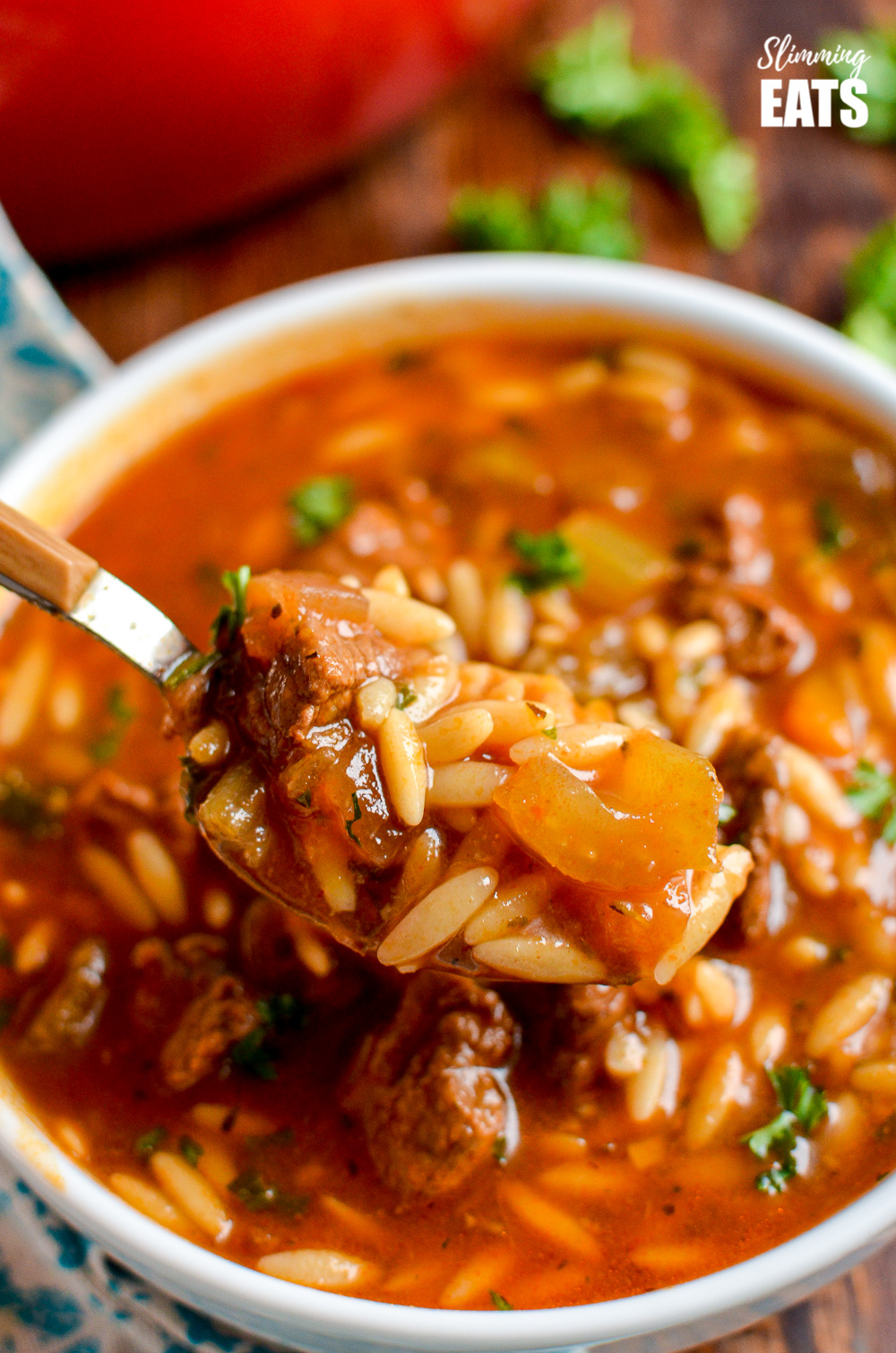 spoonful of beef celery orzo stew from white bowl