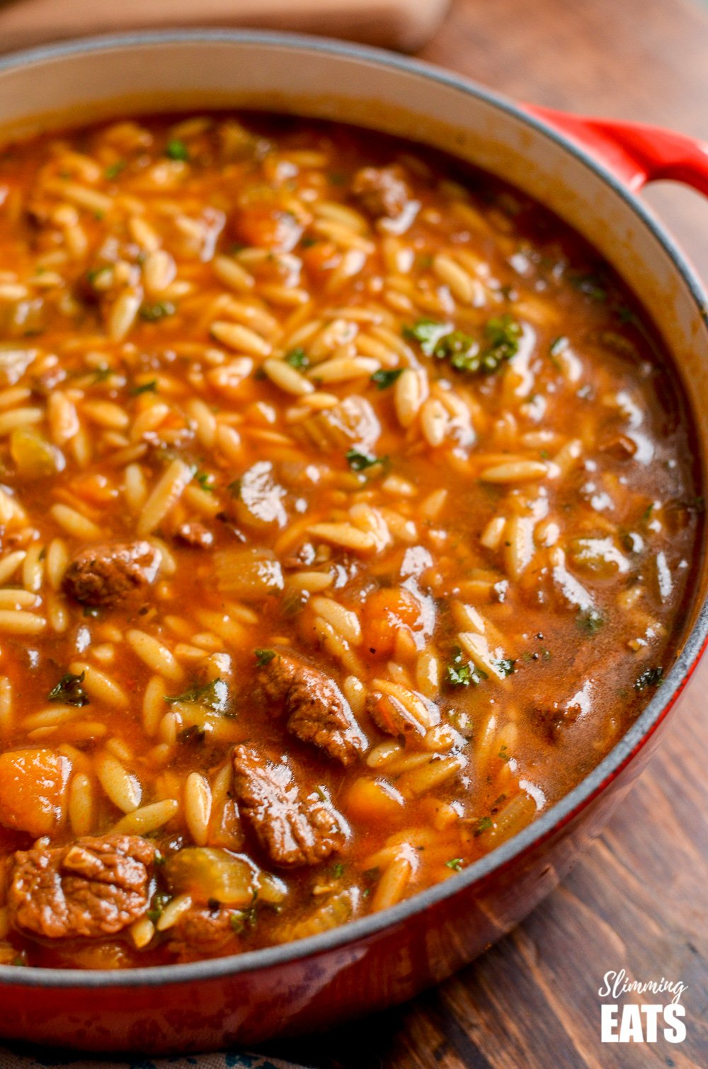 beef celery orzo stew in red dutch oven pot