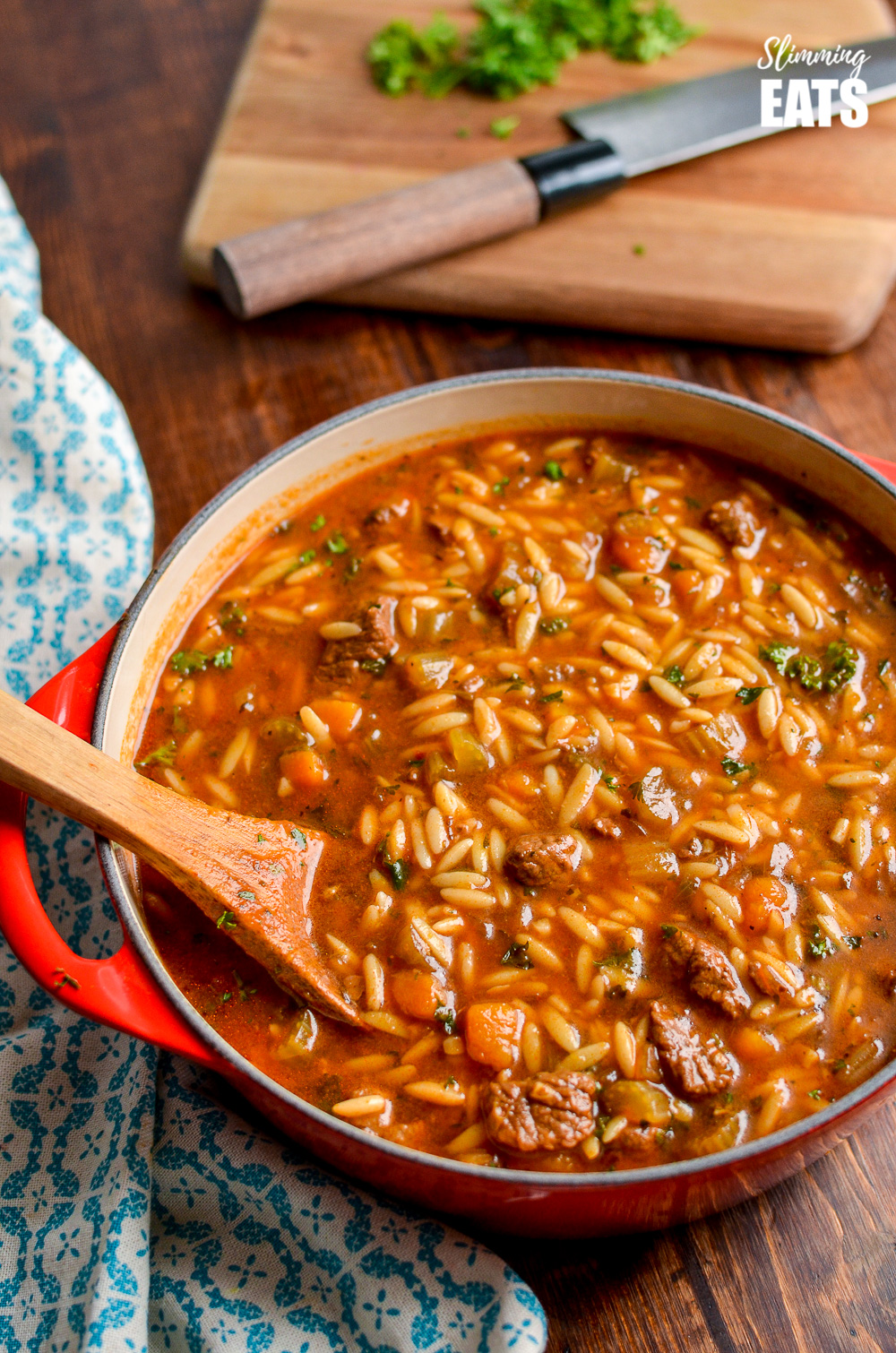 beef celery orzo stew in red dutch oven pot with chopping board and knife in background