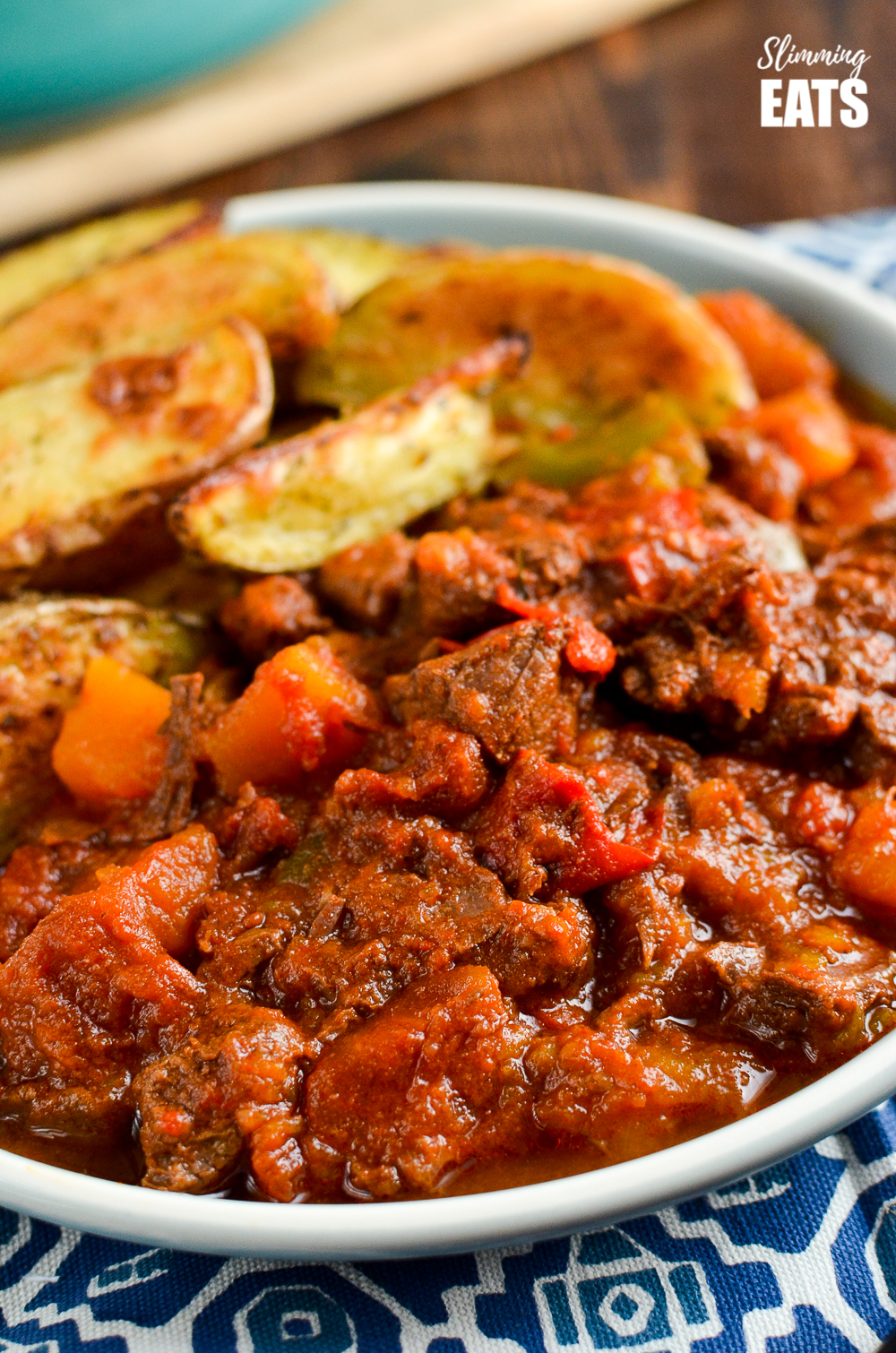 close up of paprika beef on a plate with potato wedges