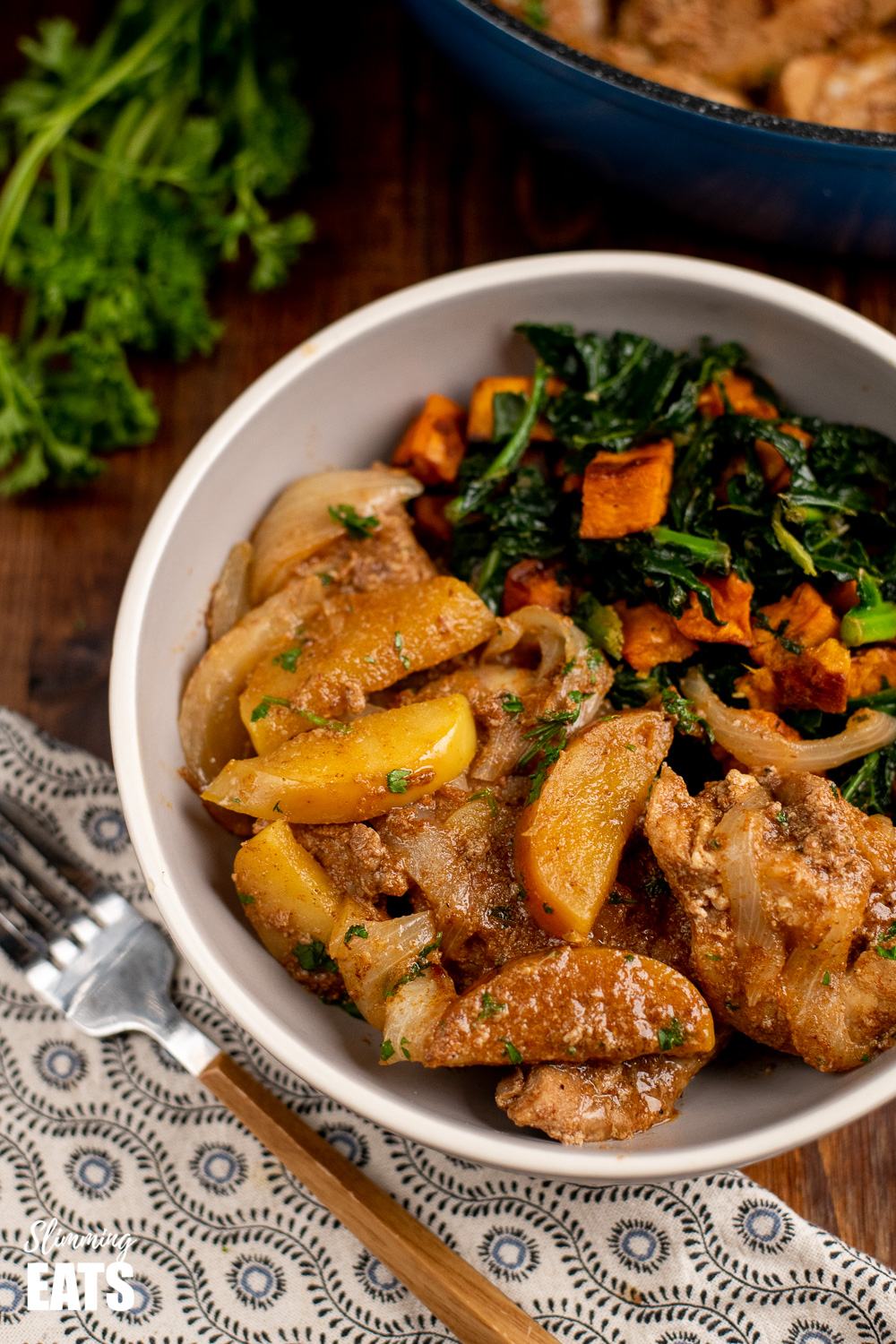 stove top pork with apples in grey bowl with kale and sweet potato and fork to the side.