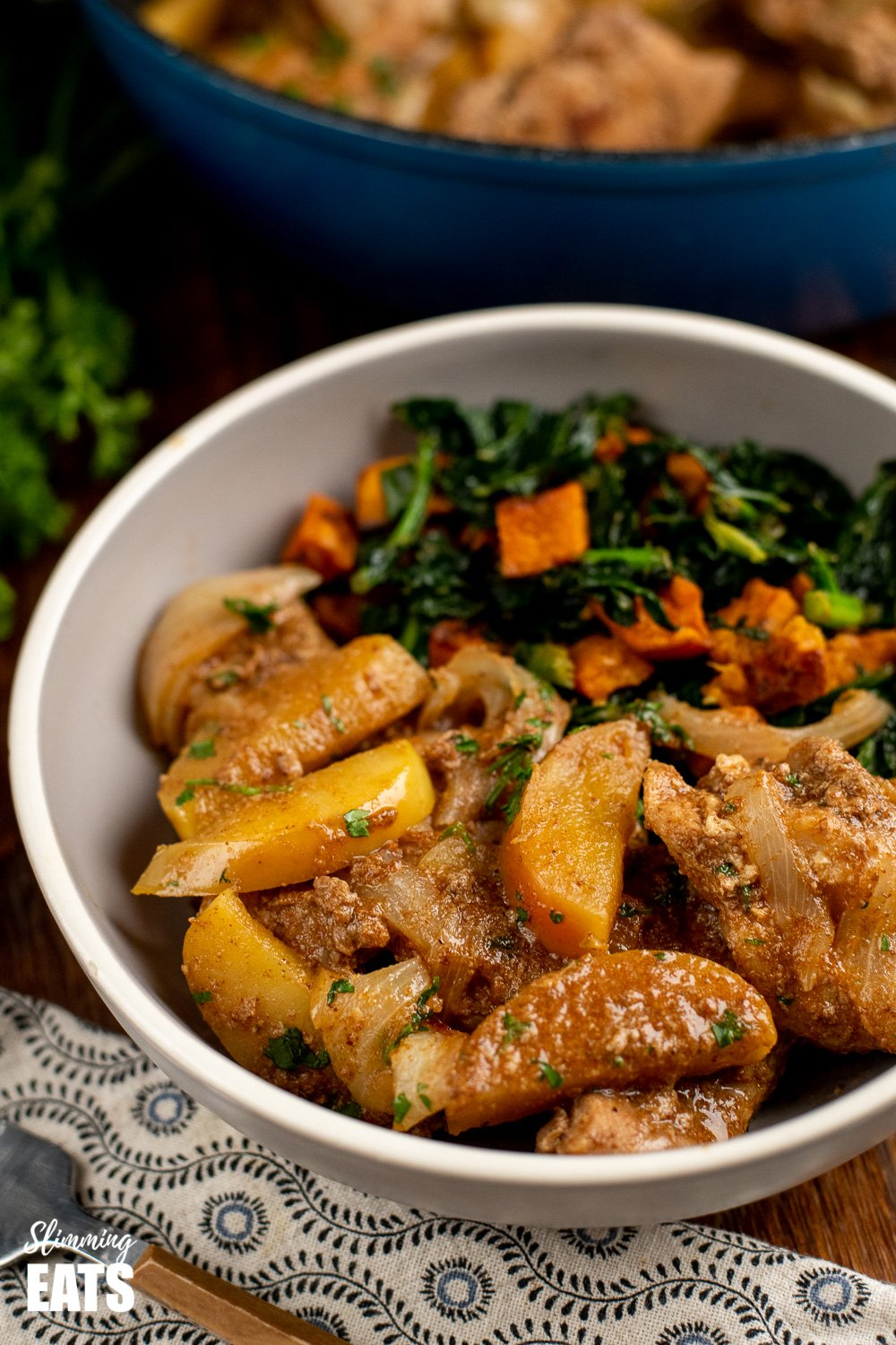 stove top pork with apples in grey bowl with kale and sweet potato