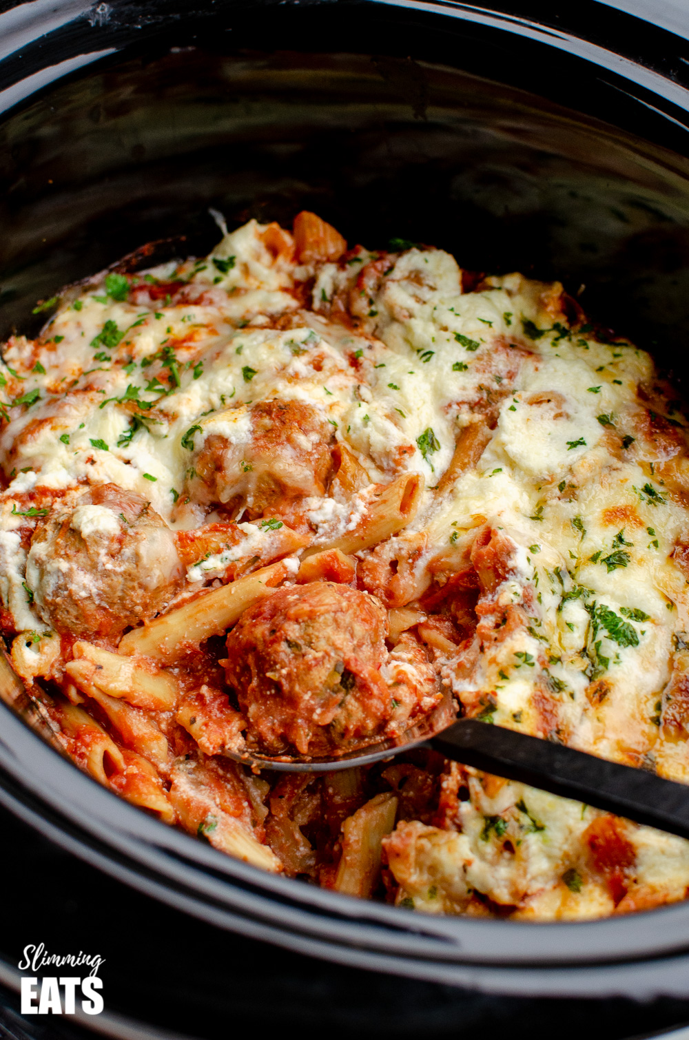 spooning meatballs out of slow cooker chicken meatball pasta bake