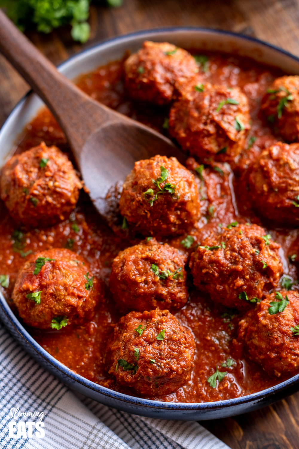 slow cooker Italian chicken meatballs in navy dish with wooden spoon on a napkin and wooden board