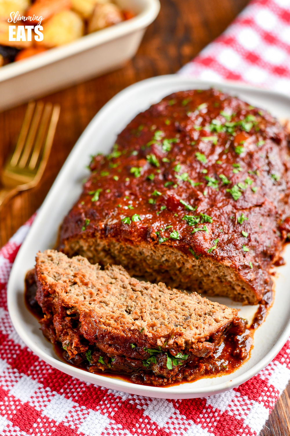 sliced slow cooker chicken mushroom meatloaf on white plate place on red and white checked napkin