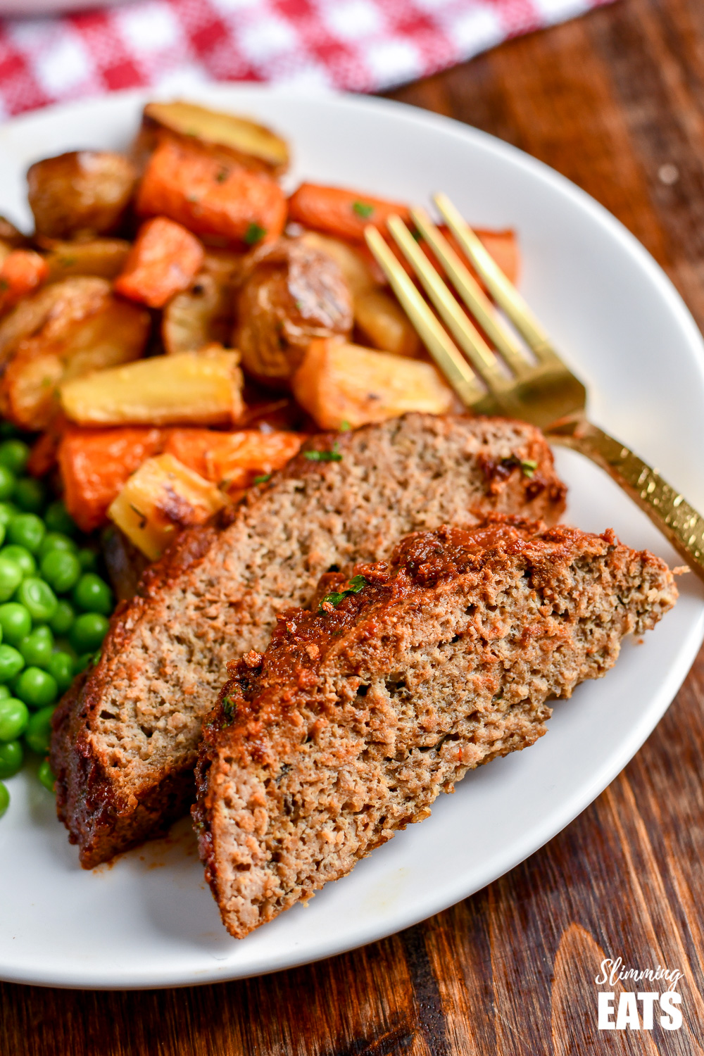 2 slices of slow cooker chicken mushroom meatloaf on white plate with roasted vegetables and peas