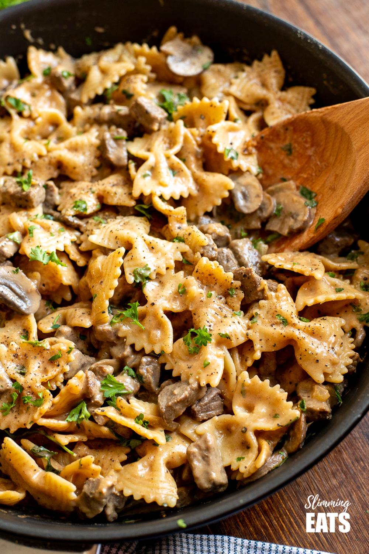 one pot beef stroganoff pasta in black frying pan with wooden spoon