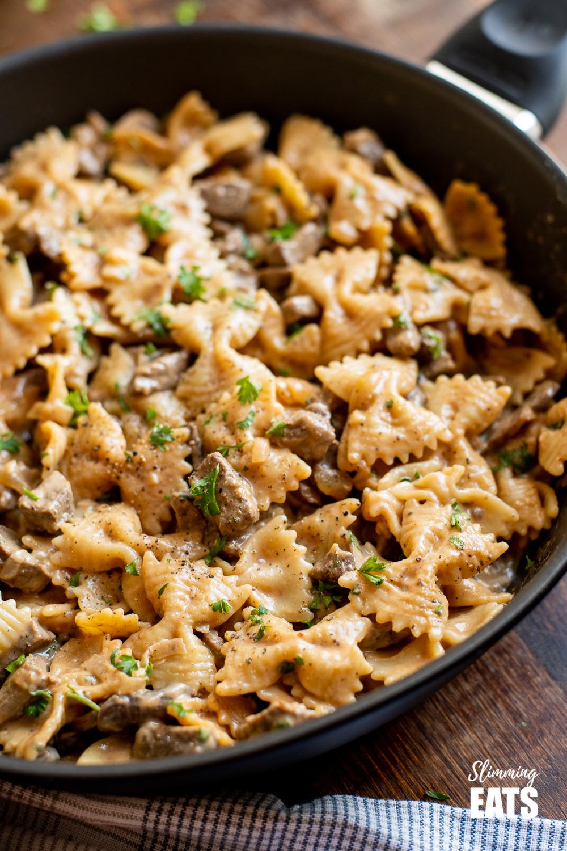 one pot beef stroganoff pasta in black frying pan on wooden board