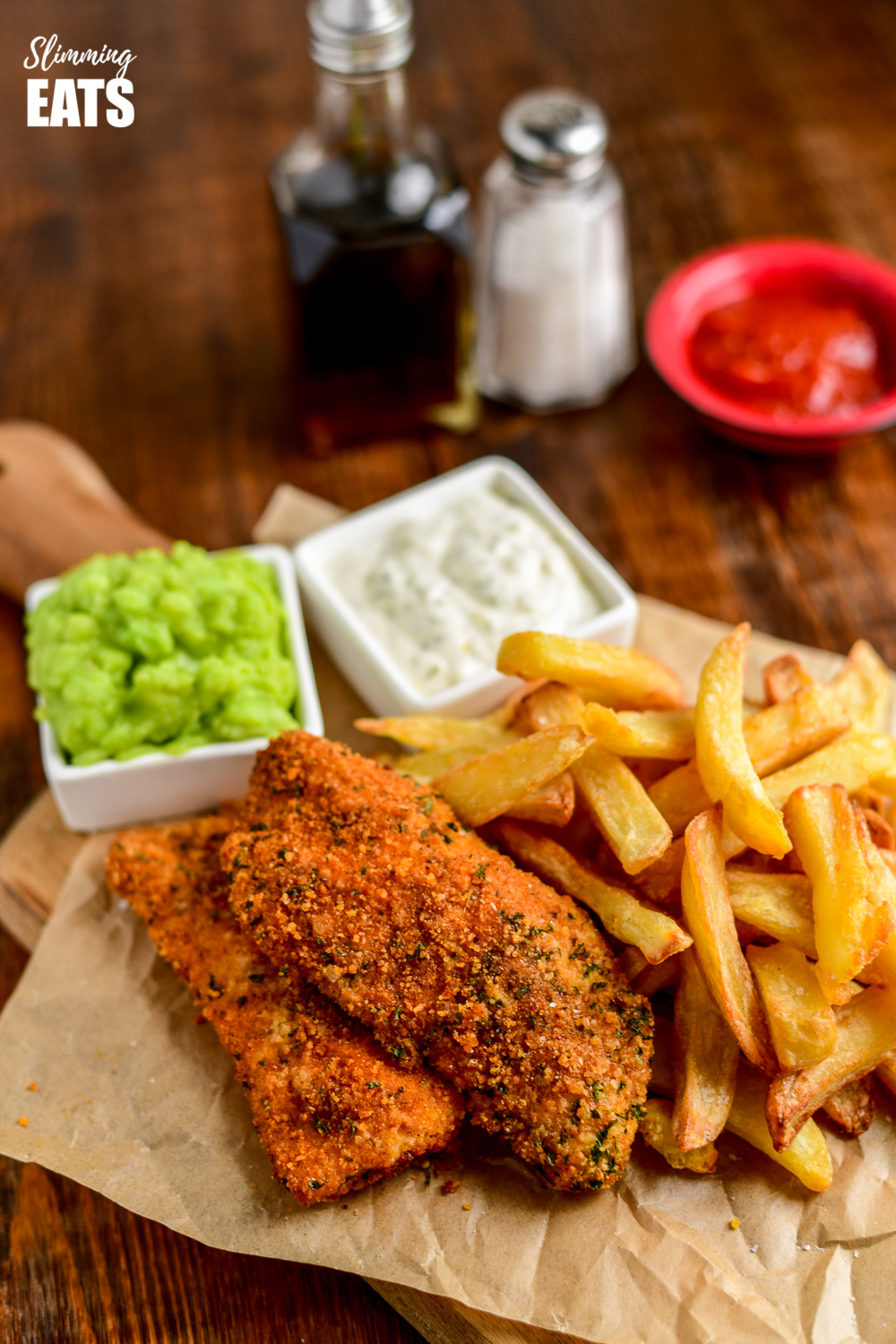 actifry fish and chips on crinkled parchment with mushy peas and tartare sauce in small white square dishes