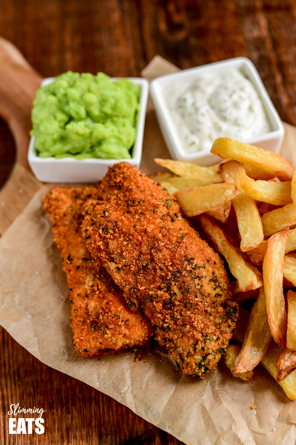 close up of actifry fish and chips with mushy peas and tartare sauce on parchment paper