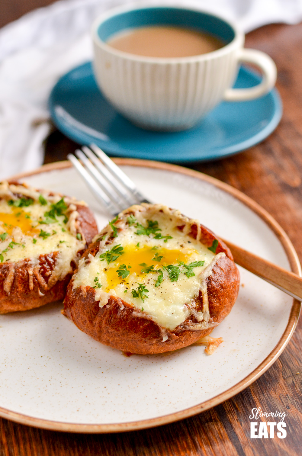breakfast roll bakes on cream plate with fork and cup and sauce in background with coffee