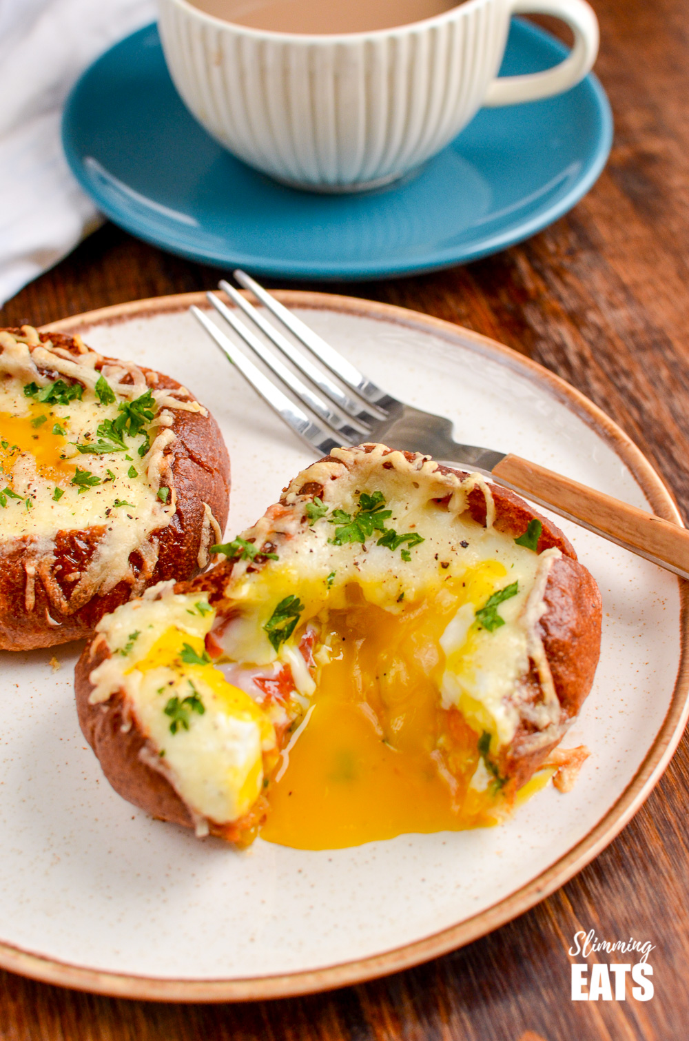 breakfast roll bakes with egg yolk burst on plate with fork