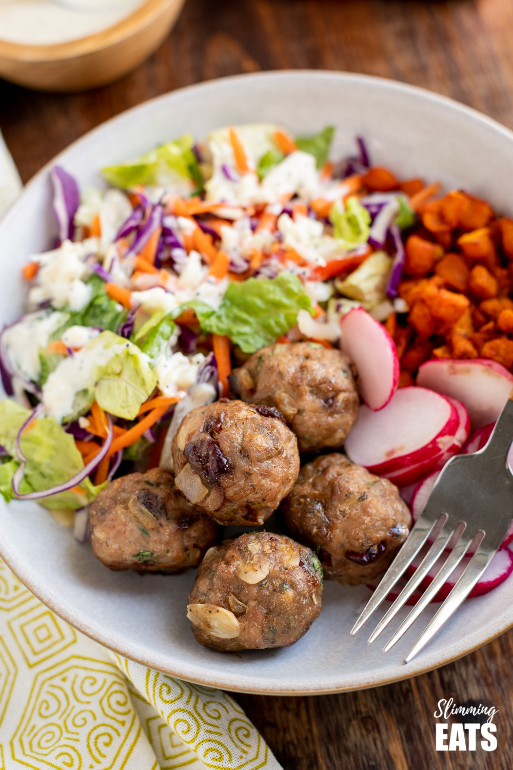 close up of cranberry almond chicken meatballs in a bowl with a mixed salad and sweet potato