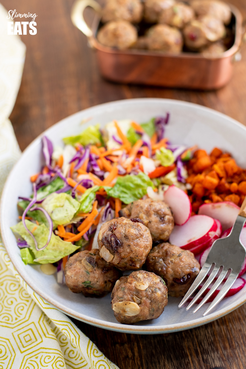 cranberry almond chicken meatballs with a mixed salad and roasted sweet potato in a bowl with a fork