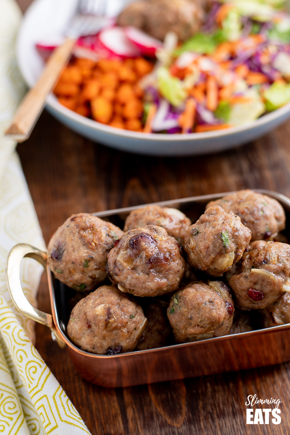 cranberry almond chicken meatballs in a copper metal tray with a bowl of salad