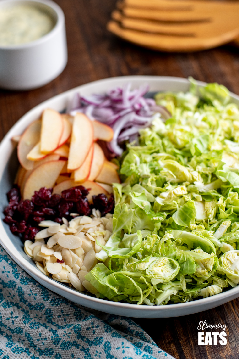 shredded brussels sprouts salad in a bowl with apples, red onion, cranberries and almonds on a wooden board