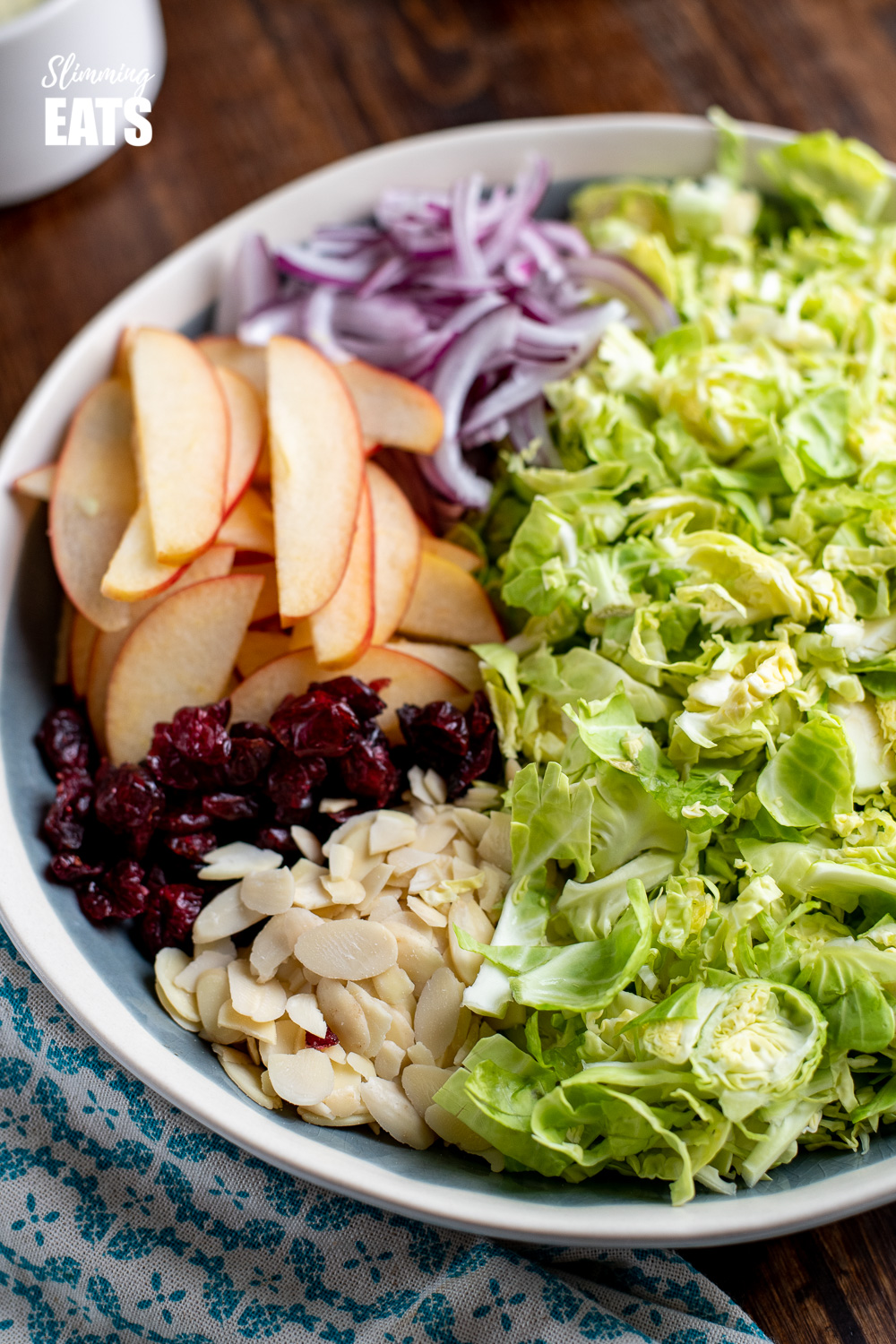 shredded brussels sprouts in a bowl with apples, red onion, almonds and cranberries