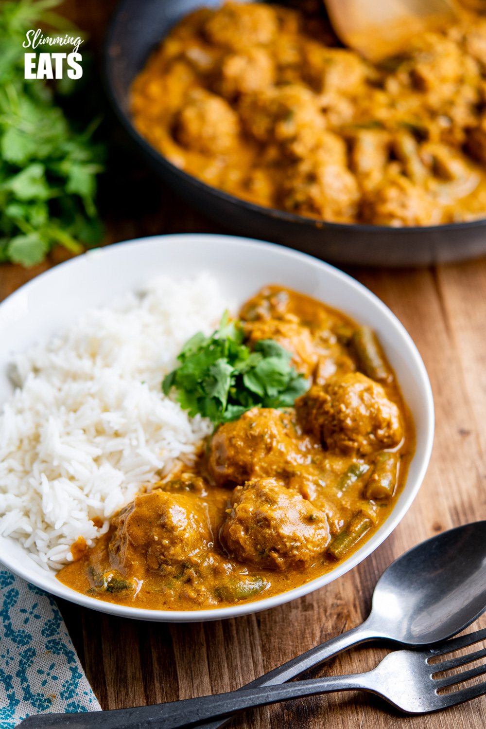 coconut beef meatballs curry in white bowl with rice and coriander