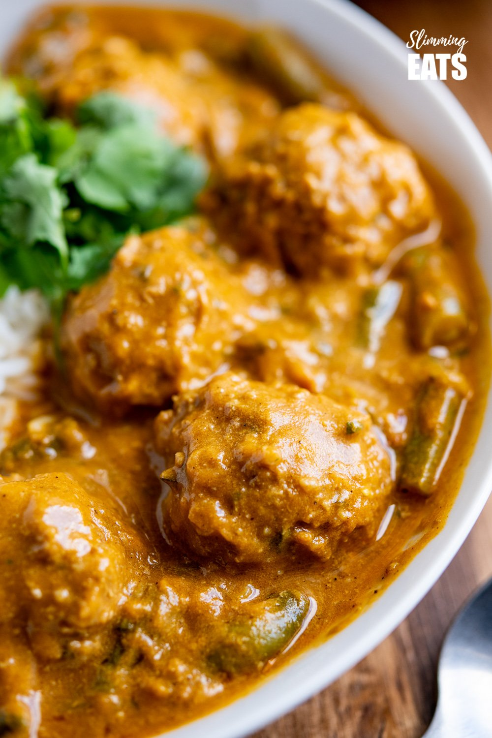 close up of coconut beef meatballs curry in white bowl with rice and coriander.