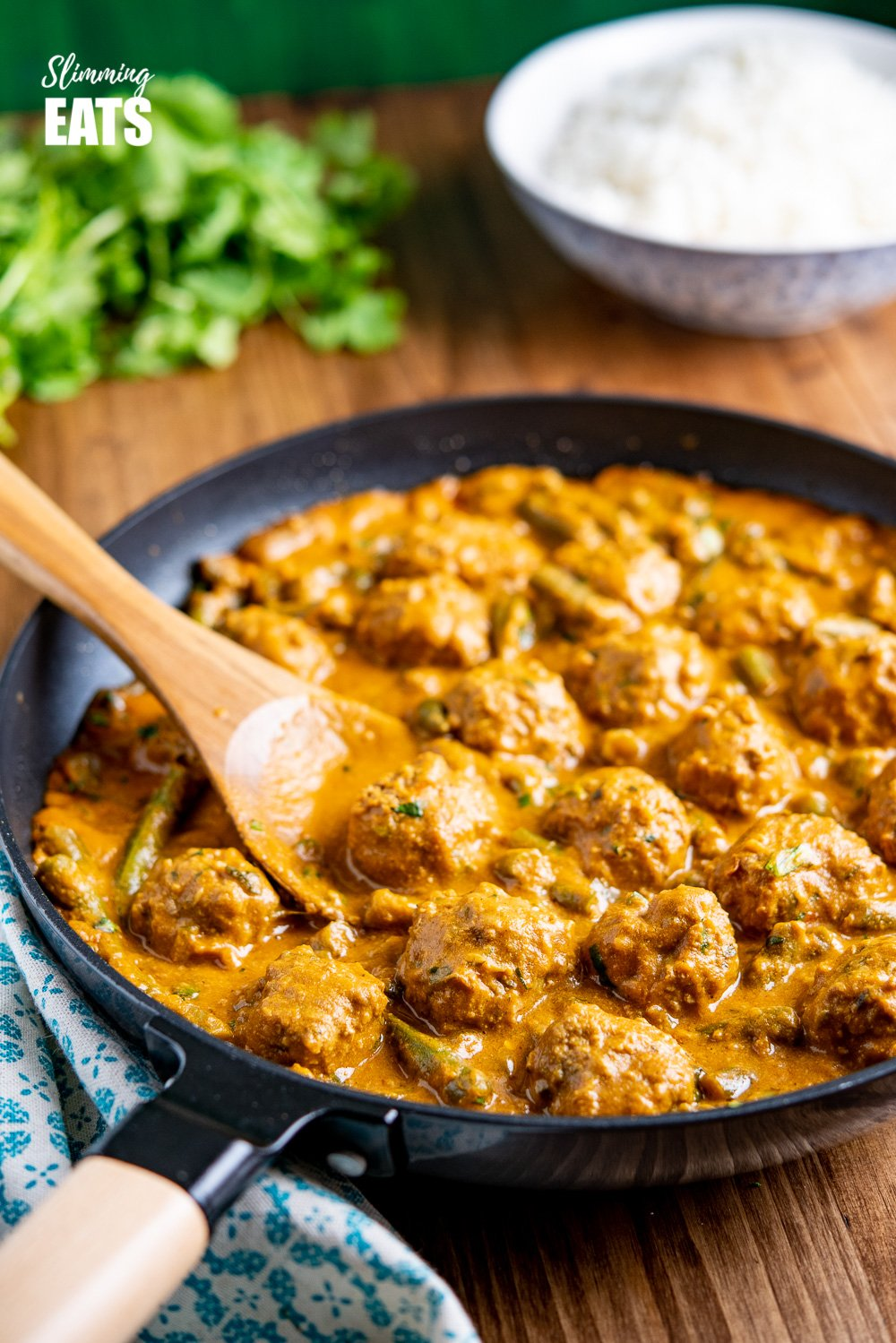 coconut beef meatball curry in black frying pan with wooden handle
