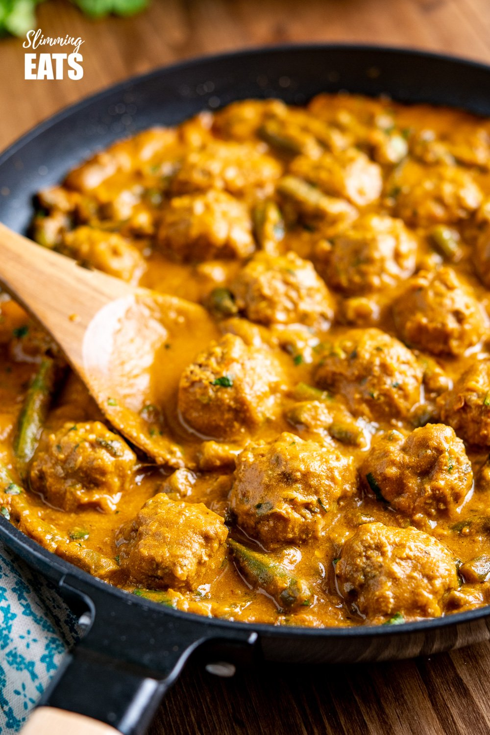coconut beef meatball curry in black frying pan with wooden spoon
