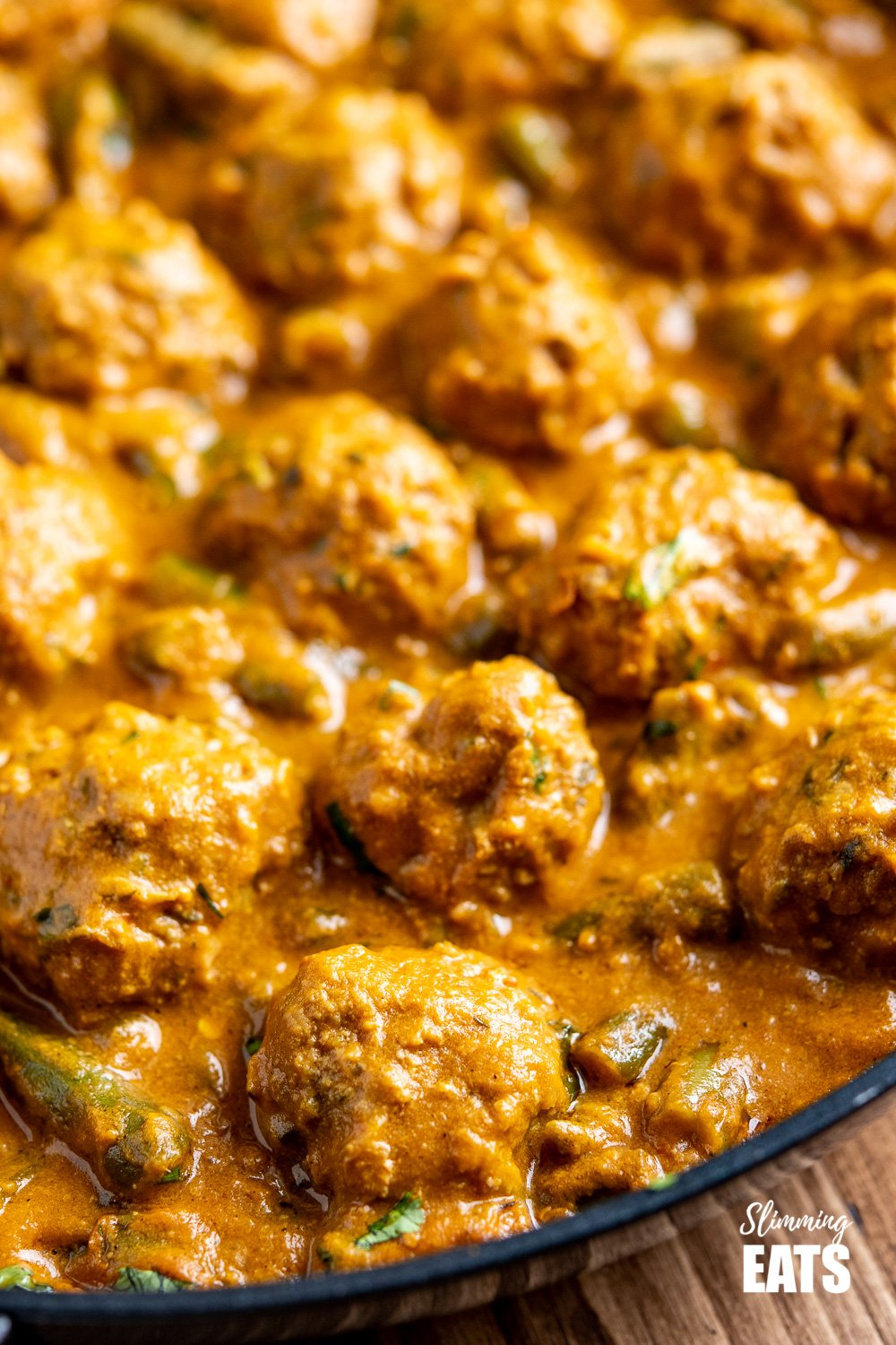 close up of coconut beef meatball curry in black frying pan
