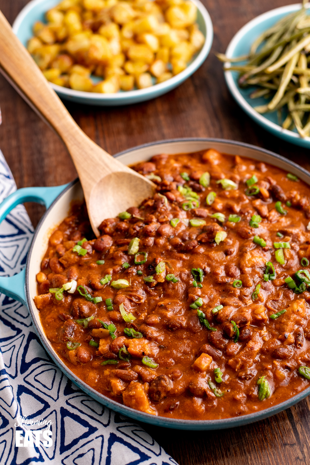 instant pot cajun pork and bean in blue cast iron shallow dish with wooden spoon
