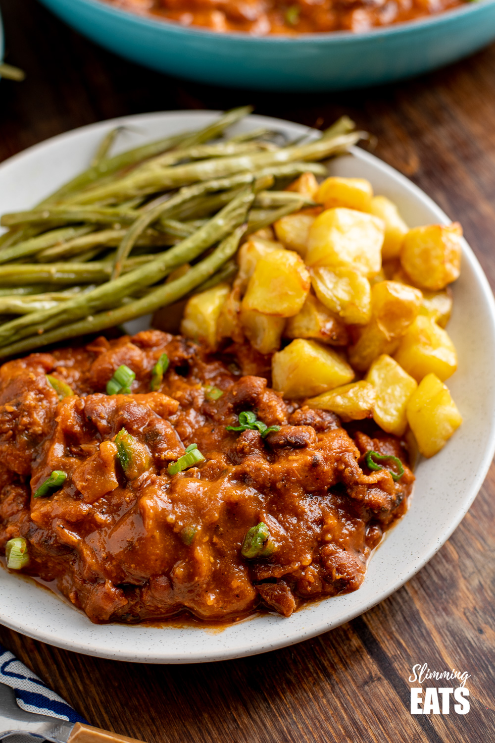 instant pot cajun pork and beans and white plate with crispy potatoes and green beans