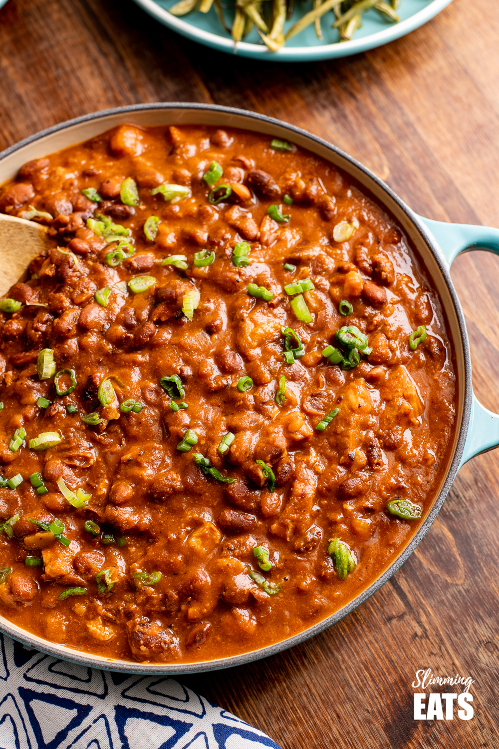 instant pot cajun pork and beans in blue cast iron pan on wooden board.