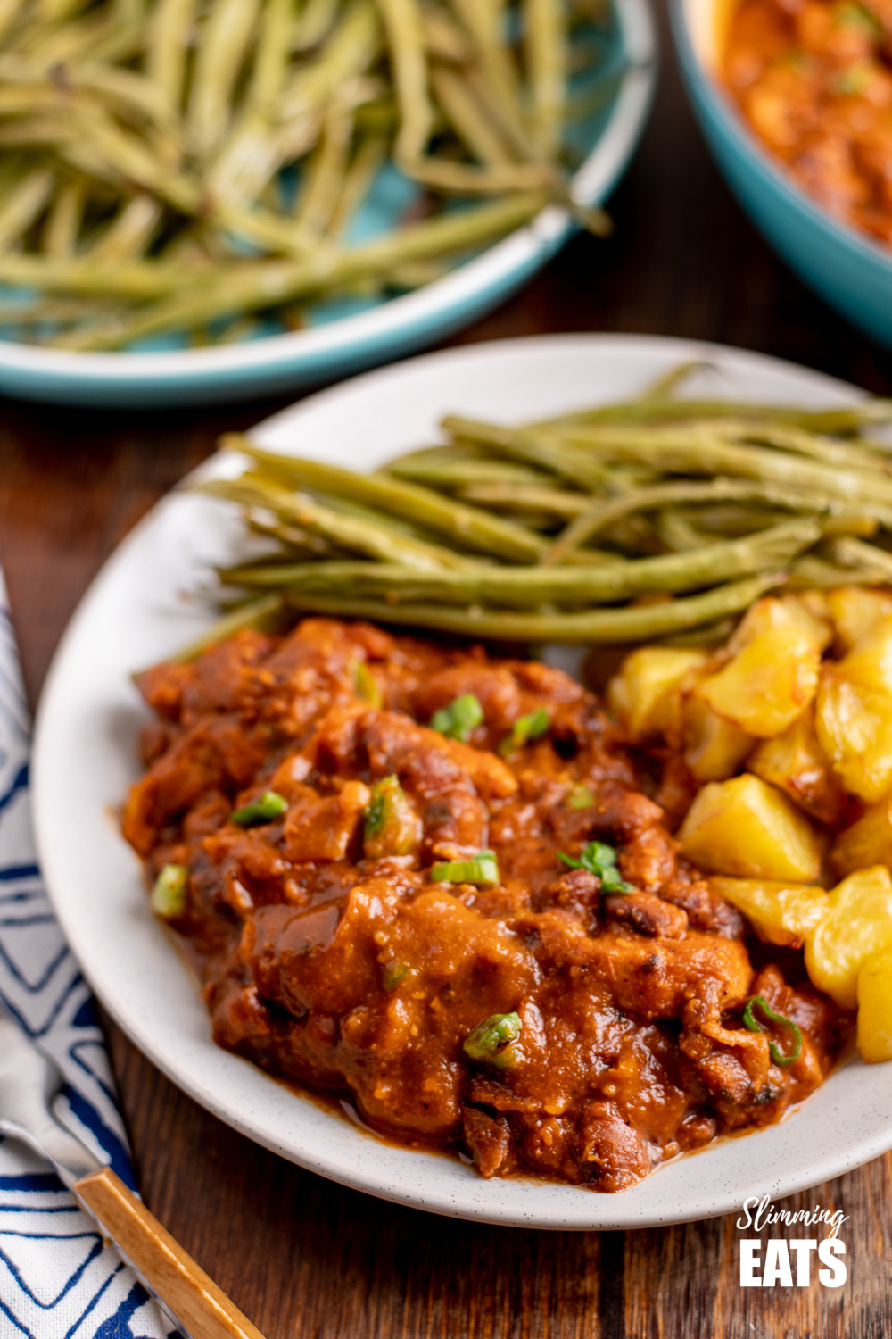 instant pot cajun pork and beans on white plate with potatoes and green beans