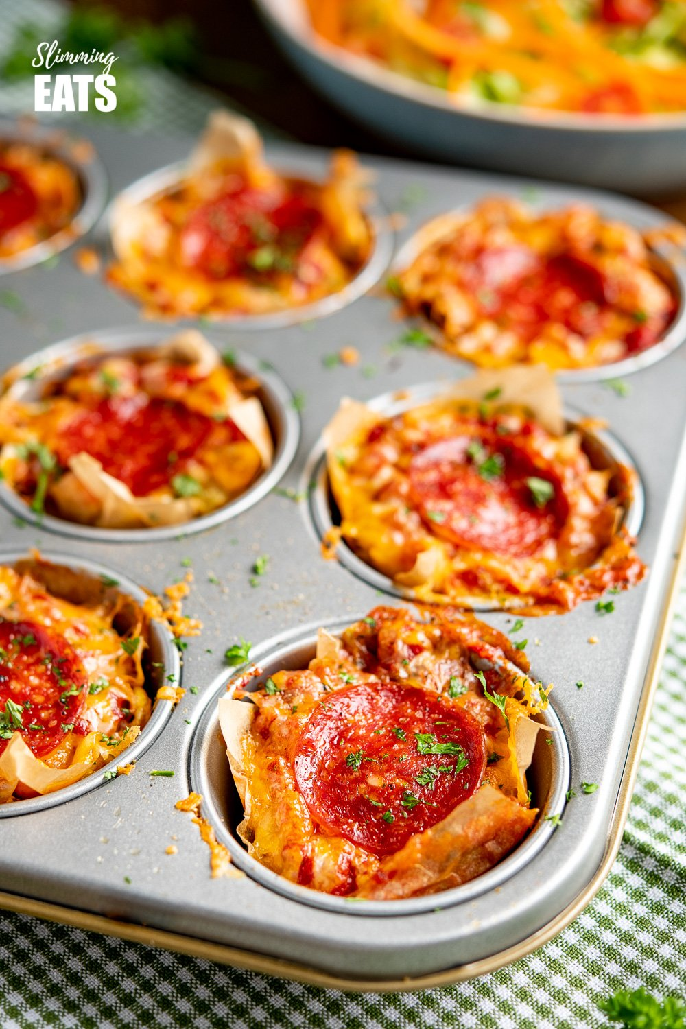 Pepperoni Pizza Egg Bites in a muffin tray on green checked towel