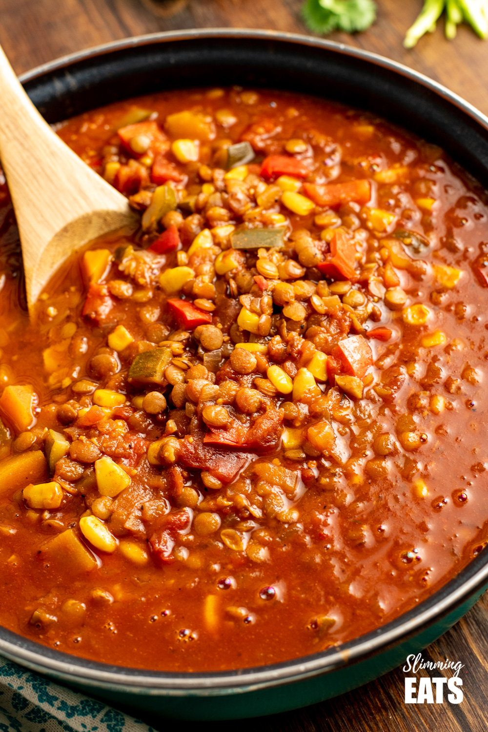 close up of taco lentil soup in frying pan with wooden spoon.
