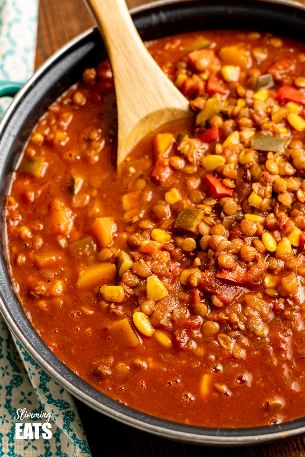 taco lentil soup in frying pan with wooden spoon.