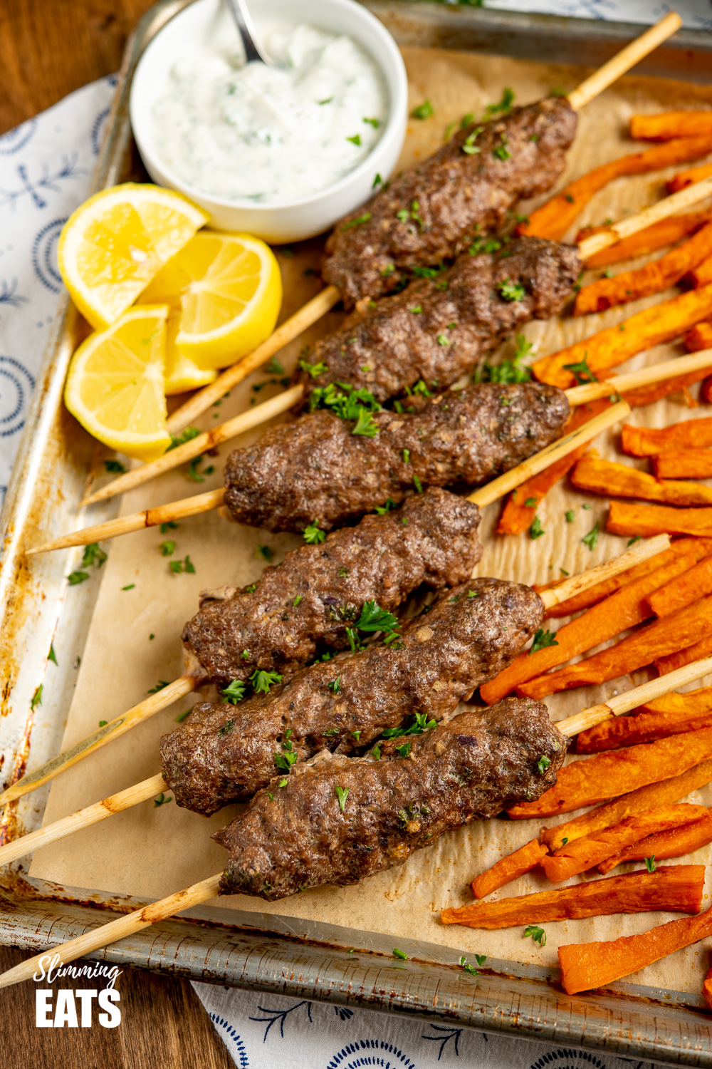 Beef Kofta Tray Bake on baking tray with white bowl of garlic sauce and lemon slices