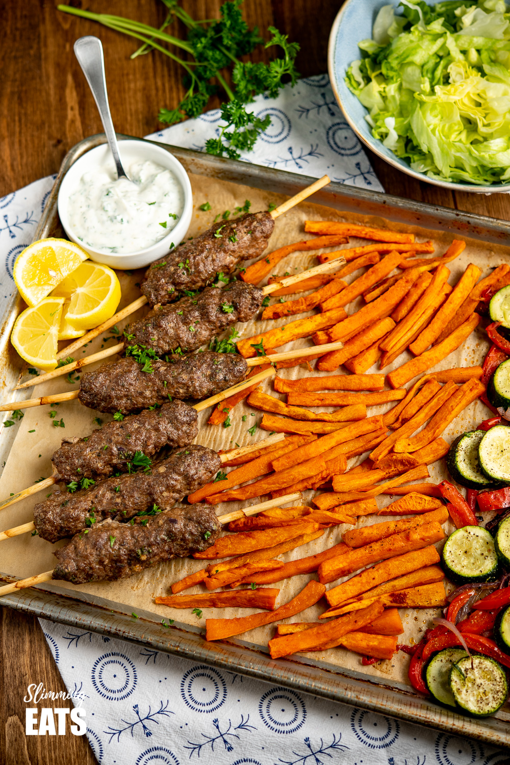 Beef Kofta Tray Bake on baking tray with white bowl of garlic yoghurt sauce and lemon slices
