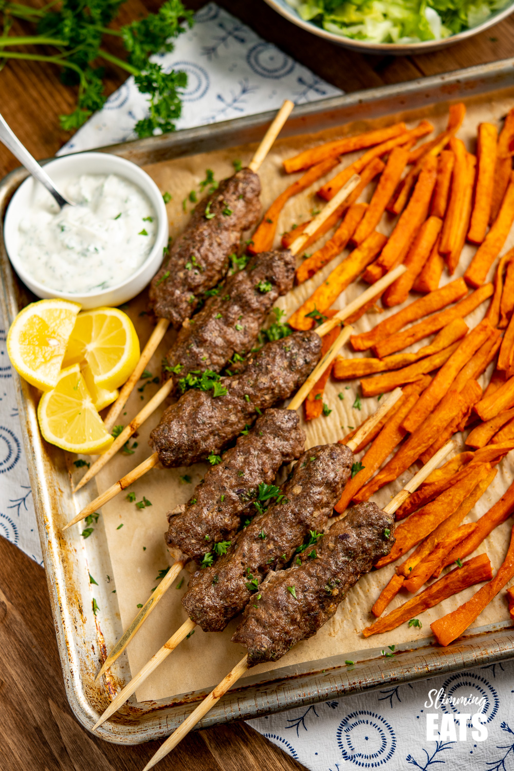 Beef Kofta Tray Bake with skewers or kofta, sweet potato fries, garlic yoghurt sauce and lemon slices on wooden board.