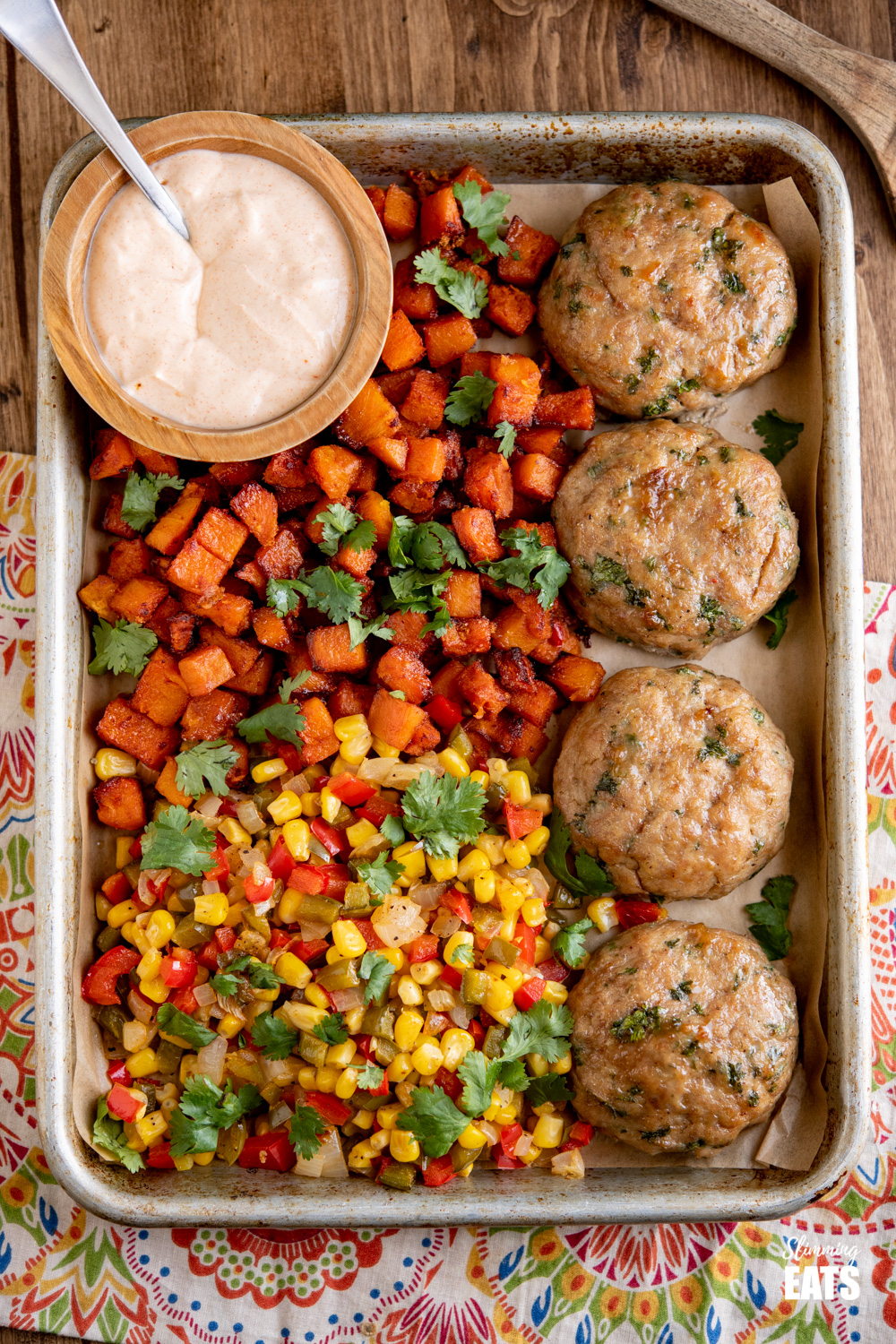 4 honey garlic chicken burgers on a baking tray with butternut squash, peppers, corn and dip