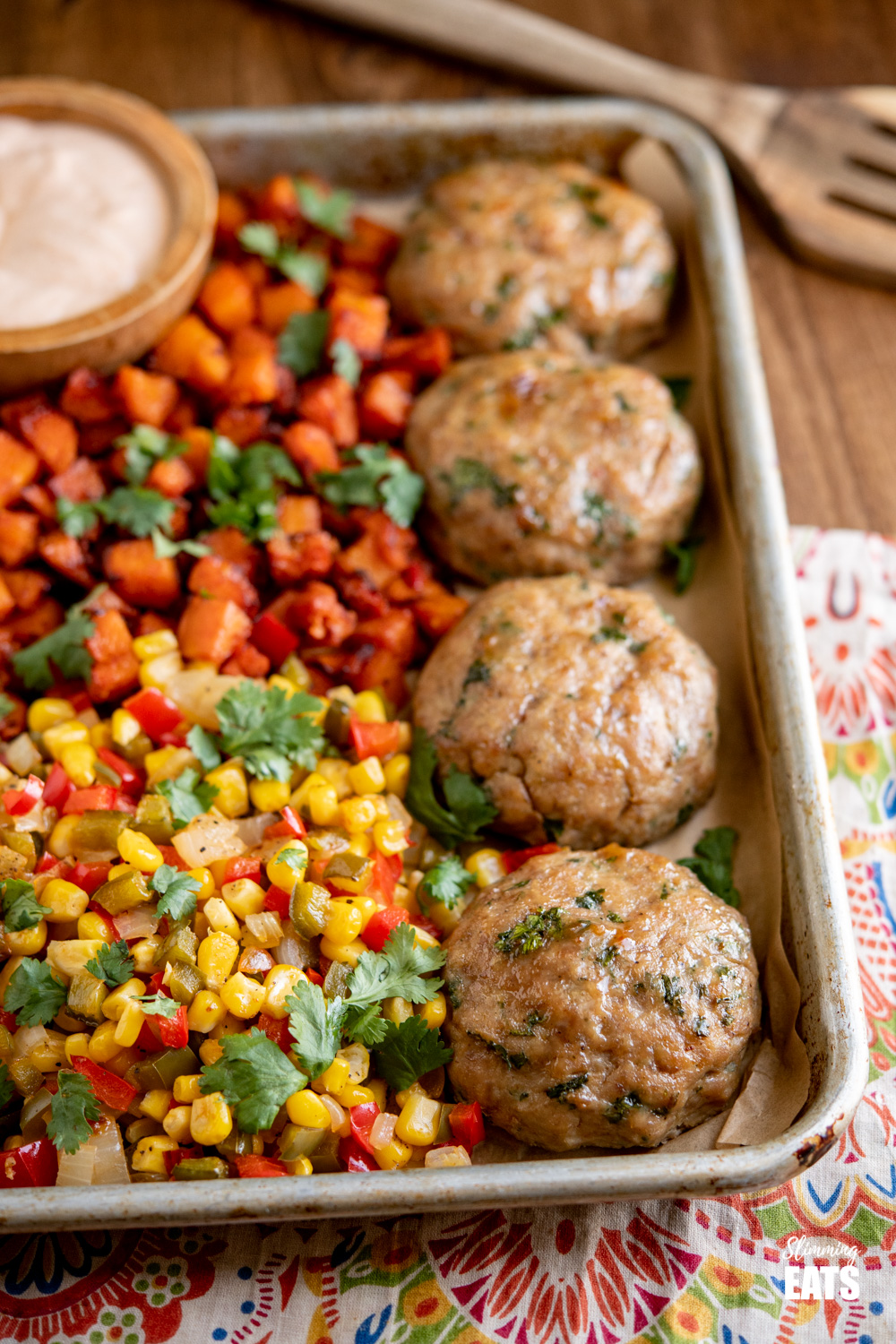 honey garlic chicken burgers on baking tray with roasted butternut squash, peppers and corn on wooden board.