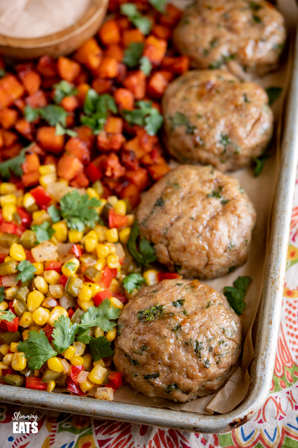 close up of burgers on baking tray with corn, peppers and butternut squash
