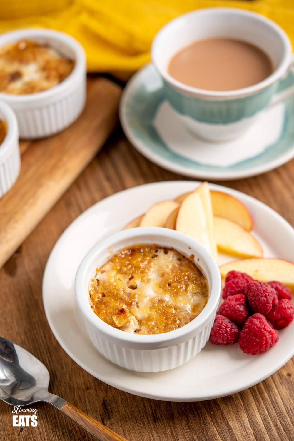 hot cross bun baked oats on white plate with raspberries, apple and cup of tea