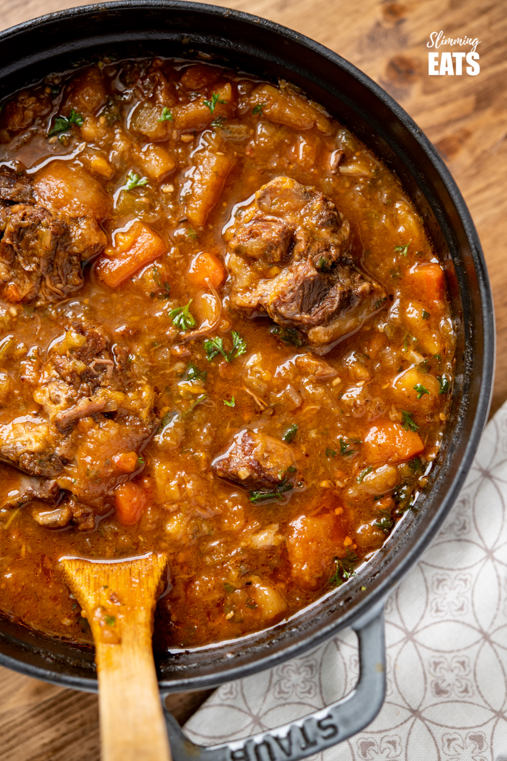 close up of Hearty Oxtail Stew in a grey staub cast iron pot with wooden spoon