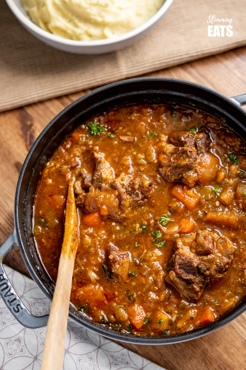 Hearty Oxtail Stew in a grey staub cast iron pot with wooden spoon