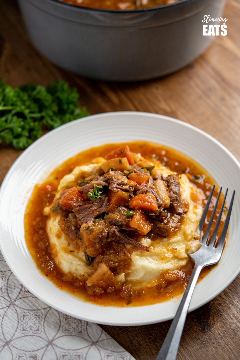 Hearty Oxtail Stew over Syn Free mashed potatoes on white plate with silver fork