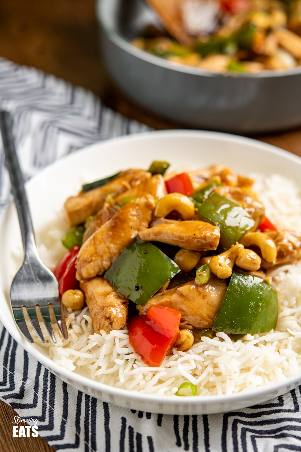 Chinese cashew chicken on white shallow bowl with rice and black handled fork