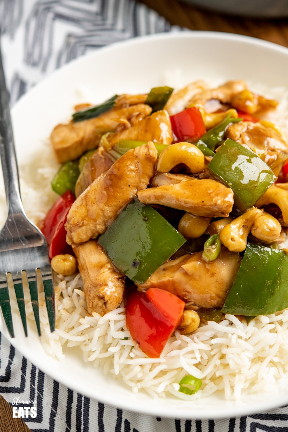 close up of Chinese cashew chicken on white shallow bowl with rice and black handled fork