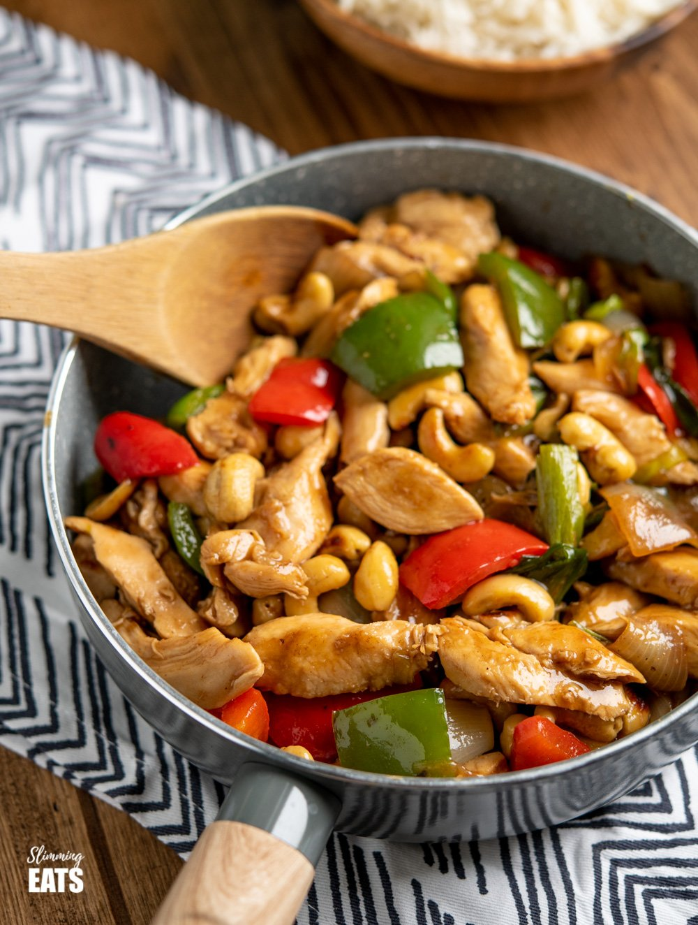 Chinese Cashew Chicken in grey frying pan with wooden spoon