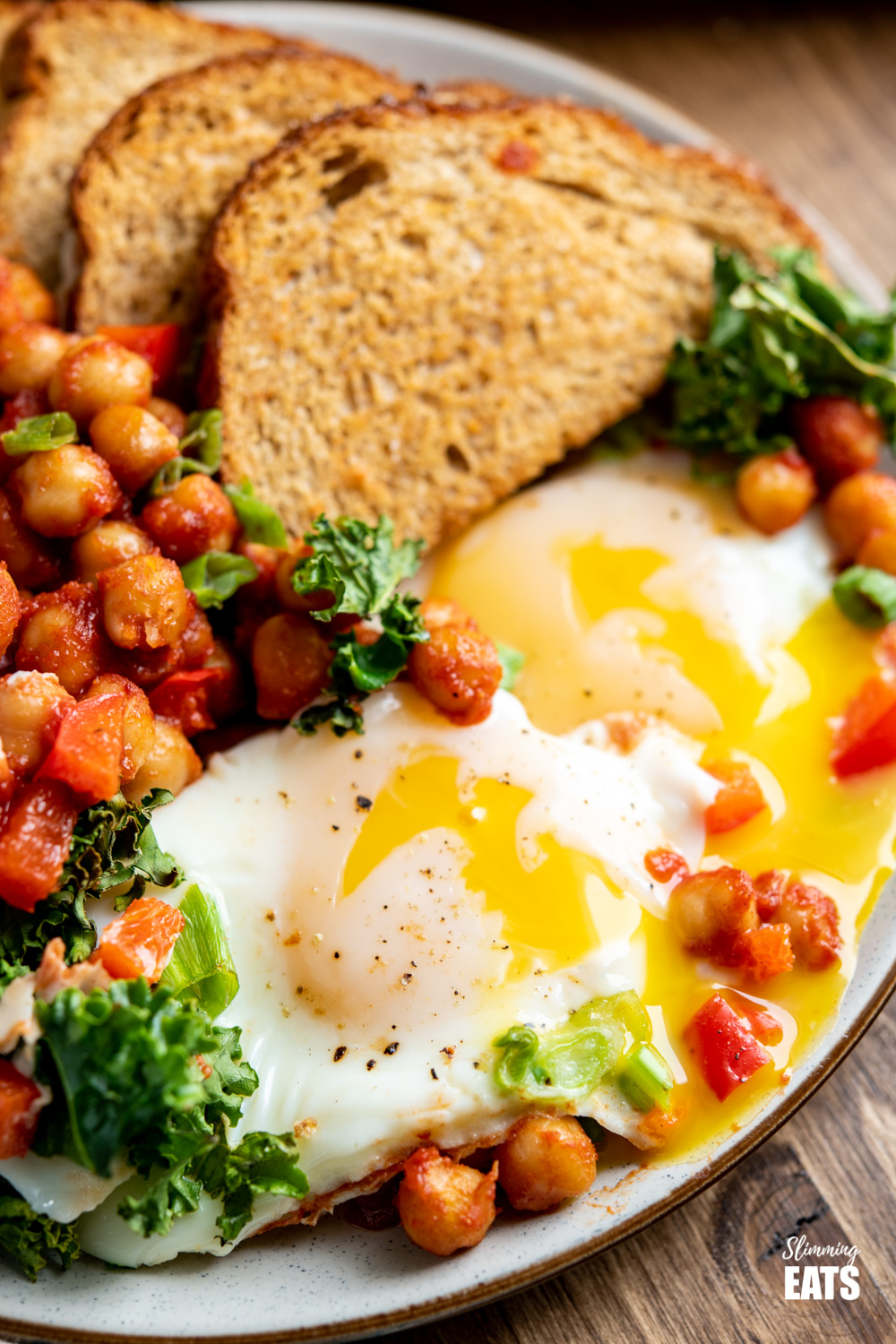 close u of eggs with chickpeas, kale, crispy toast on plate